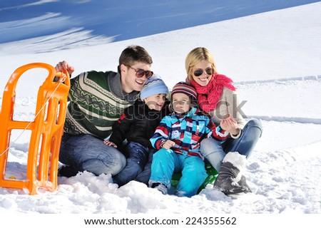 Winter season. Happy family having fun on fresh snow on vacation - stock photo