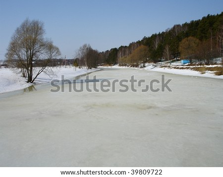 Winter season in the country. River cover with  snow and ice.
