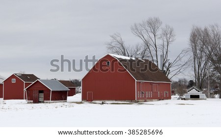Winter setting with a red barn and farm