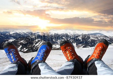 Winter shoes against sunset over the Alps - stock photo