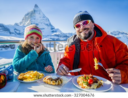 Winter, ski - skiers enjoying break for lunch - stock photo