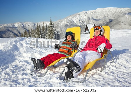 Winter, ski, sun and fun - mother with her daughter in winter resort resting in the deck chair - stock photo