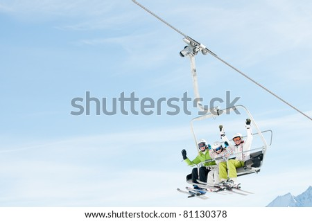 Winter - ski vacation - family on ski lift - space for text - stock photo
