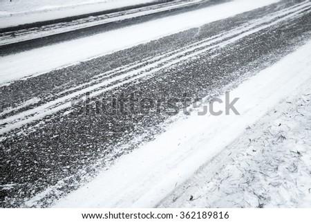 Winter slippery road background, asphalt pavement under fresh snow layer - stock photo