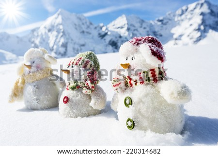 Winter, snow, Christmas - happy snowman friends and snowy mountains in background - stock photo