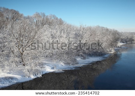 Winter snow covered trees reflection in icy river. Beautiful Christmas background. - stock photo