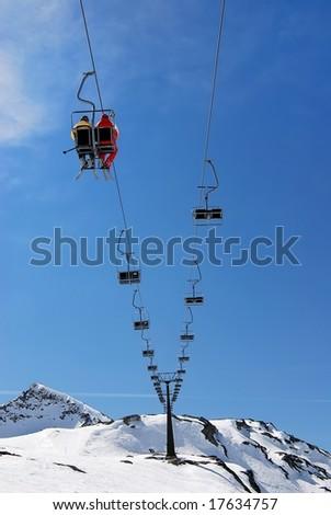 Winter snow scene of people sitting on emty ski lift - stock photo
