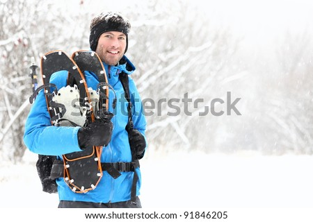 Winter snowshoeing. Young outdoorsman hiker standing smiling happy holding snowshoes outside in the snow during snowshoe hiking trip. From Quebec, Canada. - stock photo