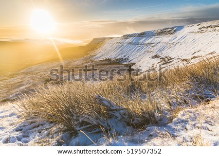 Winter snowy landscape at sunrise in Wales. Snow covering hills in the early morning. Frozen grass on foreground. Nature and weather concepts.