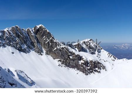 Winter snowy mountain peak and blue sky - stock photo