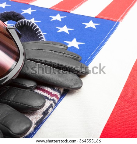 Winter sport goggles and gloves over US flag - close up studio shot