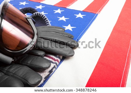 Winter sport goggles and gloves over US flag - studio shot