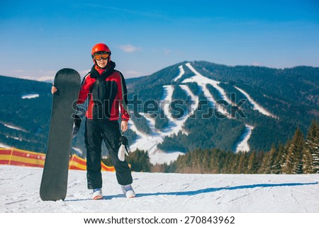 Winter sports. Young woman snowboarder posing against mountain with the slopes at ski resort - stock photo
