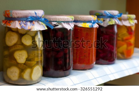 Winter stores. Jars with paprika, cucumber, chili pepper, olives, cherry