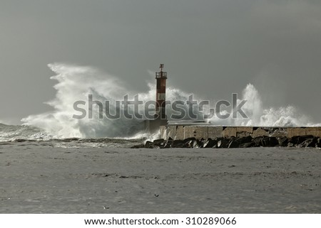 Winter stormy seascape from the north of Portugal with big waves over beacon and pier. Ave river mouth, Vila do Conde. - stock photo
