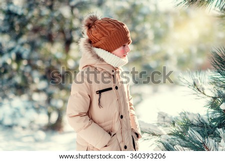 winter sunny day in the snowy forest walks boy in a cap with red cheeks - stock photo