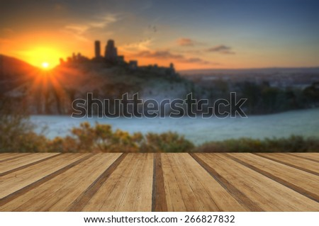 Winter sunrise over landscape with Castle with wooden planks floor - stock photo