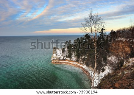 Winter sunset at Miners Castle, Pictured Rocks National Lake-shore.  Beautiful clear, emerald Green water, in Michigan's Lake Superior. - stock photo