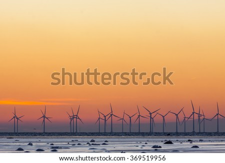 Winter sunset at Oresund between Denmark and Sweden and an offshore wind park in the background. In the foreground icy surfaces close to the beach - stock photo