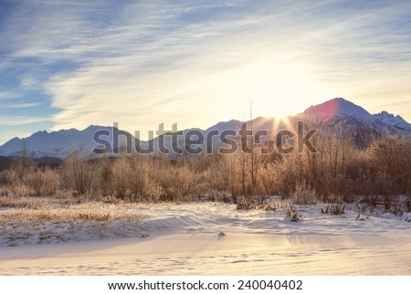 Winter sunset behind the Chilkat mountains in Southeast Alaska with light snow on the ground.