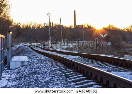 Winter sunset on railroad in countryside. First snow on railway. - stock photo