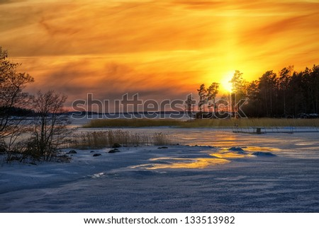 Winter sunset reflections from iced sea with red houses in the distance - Sweden - stock photo