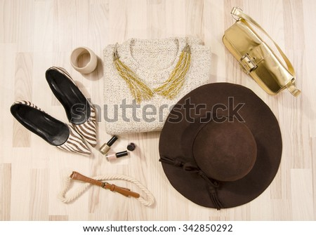 Winter sweater and accessories arranged on the floor. Woman brown with gold accessories, high heels, hat, necklace and purse. - stock photo