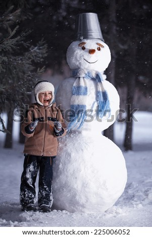 Winter. The boy laughs, standing next to a snowman.Carrots instead of the nose, the bucket on his head. - stock photo