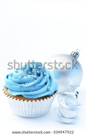 Winter theme blue silver cup cake with christmas bauble and ribbon - stock photo