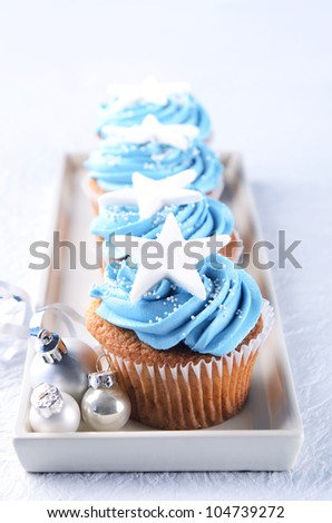 Winter theme christmas cupcakes with blue icing and silver xmas baubles - stock photo