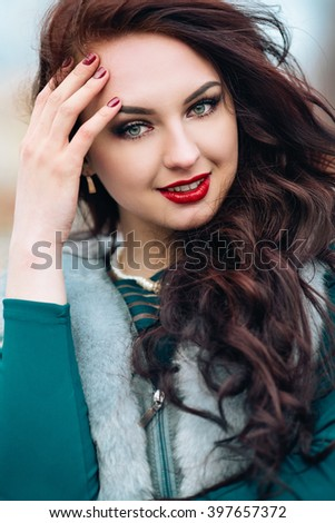 Winter time fashion for women. Woman wearing sweater fur vest belt and pendant in freezing cold time. Excellent Bright Makeup, red puffy lips, long dark hair, the girl has fun - stock photo
