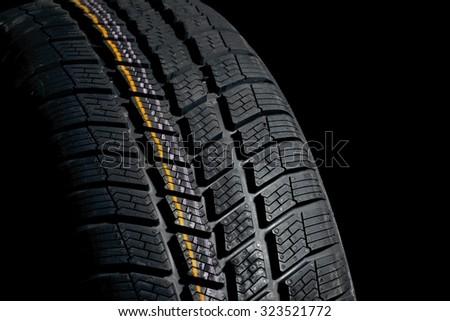 Winter tire closeup, dark backgroud - stock photo