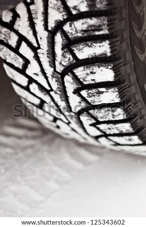 Winter tire on the snow road - stock photo