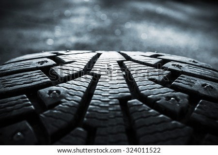 Winter tires photographed in close-up view in Finland. Focus point is in the center of the image numbers. The front and back of the image out of focus. Image includes a heavy effect. - stock photo