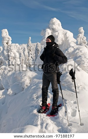 Winter tourist with snowshoes during a beautiful sunny day. - stock photo
