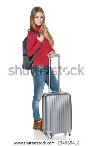 Winter traveler. Full length of young female in casual standing with the suitcase and backpack, isolated on white background