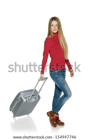 Winter traveler. Full length of young female in casual walking with the suitcase, isolated on white background
