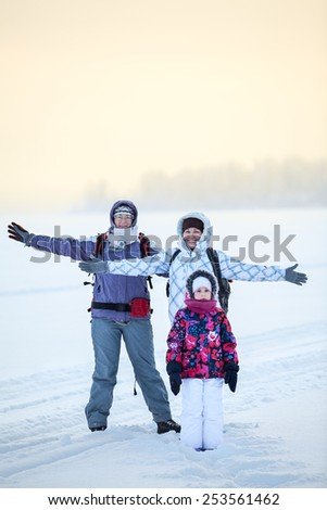 Winter travelers standing on ice of frozen lake in warm clothes and smiling - stock photo