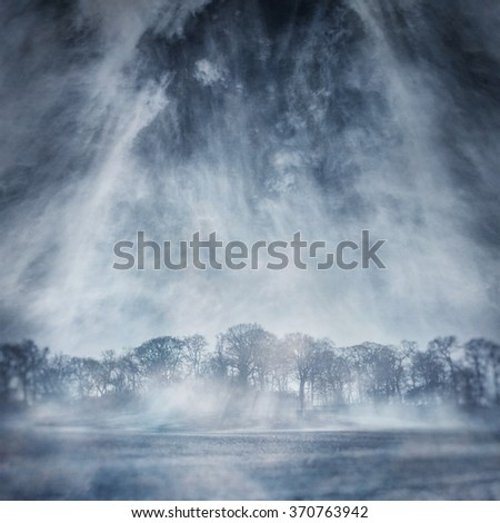 Winter trees in a frozen, misty landscape captured using long exposure, bokeh and other effects with some areas blurred to create a surreal and dreamlike effect.