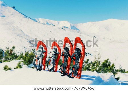 Winter trekking in the mountains. Snowshoes stand in the snow against the backdrop of the mountain.