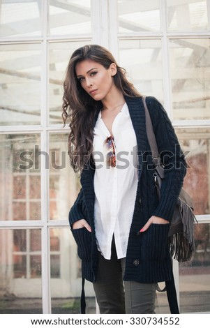 winter trendy fashion young woman in dark blue cardigan, white shirt and green pants, stand in front glass doors - stock photo