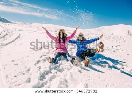 winter, two cheerful young girls having fun in the snow in the mountains - stock photo