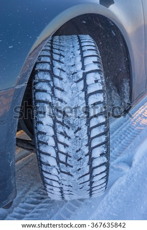 Winter tyre on the road covered with snow - stock photo