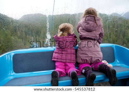 Winter vacation - Children in winter ski lift looking at view