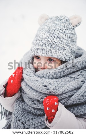 winter vertical portrait of cute toddler girl on the walk in grey knitted hat and scarf - stock photo