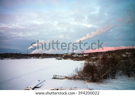 Winter view at river shore and tubes of Pulp and paper Mills, Kondopoga, Russia.
