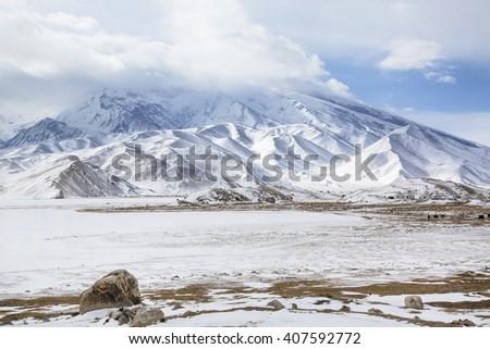Winter view of Mustagh Ata Mountain at Karakul Lake on the Karakoram Highway in Pamir Mountains, Akto County,Kizilsu Kirghiz Autonomous Prefecture, Xinjiang, China - stock photo