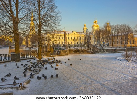 Winter view of St. Nicholas Naval Cathedral, Baroque Orthodox cathedral in Saint Petersburg, Russia with old bridge and pigeons on the foreground - stock photo