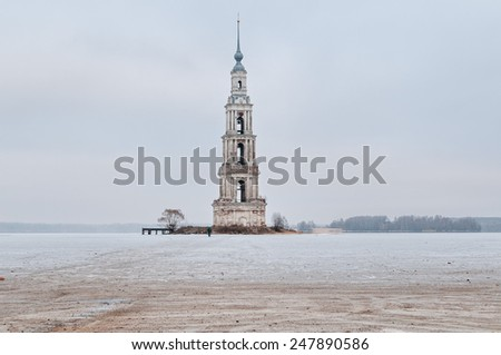 Winter view on the famous drowned belfry of St. Nicholas cathedral (1800) standing in middle of frozen reservoir against cloudy sky background. Kalyazin, Tverskaya region, Russia.   - stock photo