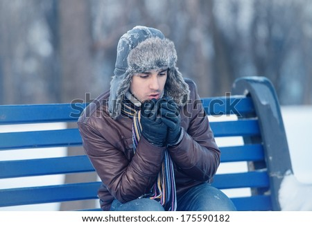 Winter walk - young man in an ear flap hat sitting on a bench and warming his hands - stock photo